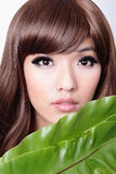 Woman face and green leaf Stock Photos