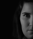 Woman face half close up serious Stock Image