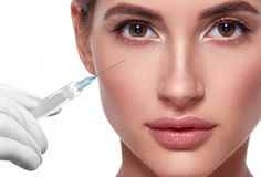 Woman face and hand in glove with syringe making injection Royalty Free Stock Images