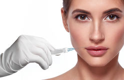 Woman face and hand in glove with syringe making injection Royalty Free Stock Photos