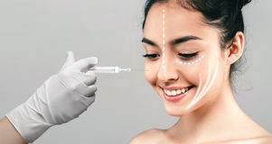 Woman face and hand in glove with syringe making injection. People, cosmetology, plastic surgery and beauty concept - beautiful young woman face and hand in Royalty Free Stock Photos