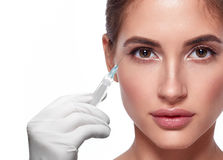 Woman face and hand in glove with syringe making injection. People, cosmetology, plastic surgery and beauty concept - beautiful young woman face and hand in stock images