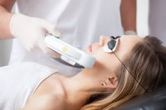 Woman during face laser therapy in cosmetics Stock Images