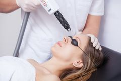 Woman during face laser therapy in cosmetics Royalty Free Stock Images