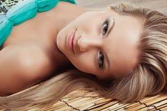 Woman face laying on bamboo mat Stock Photo