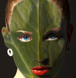 Woman face with leaf texture and blue eyes. Ecology concept. stock photo
