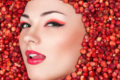 Woman face licking lips lying in wild strawberry. Fashion woman face licking lips lying in wild strawberry Royalty Free Stock Images
