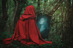 Woman face in a magical mirror. Dark fantasy and surreal Stock Photos