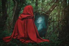 Woman face in a magical mirror stock photos
