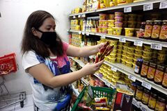 Woman with face mask buy food supplies at a grocery store during the Covid 19 virus outbreak
