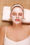 A woman with a face mask. A woman with a face mask, laying on a towel on a bamboo mat Royalty Free Stock Photos