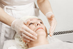 Woman at face massage Stock Images