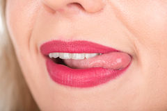 Woman Face with Open Mouth And Tongue Out. Bright Red Lipstick in Use and White Teeth. Royalty Free Stock Photography