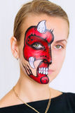 Woman face with painted devil mask on it  on white background Stock Images