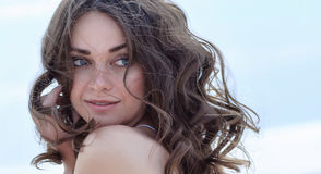 Woman face Portrait on the beach. Happy beautiful curly-haired girl close-up, the wind fluttering hair. Spring portrait on the bea stock image