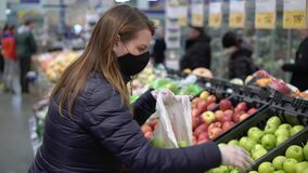 Woman in face protective mask in supermarket grocery store covid-19 coronavirus