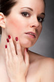 Woman face with red fingernail Stock Photography