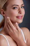 Woman face skincare. Beautiful woman putting cream on her cheek, face skincare Royalty Free Stock Photography