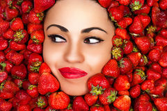 Woman face in strawberries Stock Photos