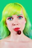 Woman face with sweet cherry hanging from mouth on green background Royalty Free Stock Image