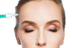 Woman face and syringe making injection Stock Photo