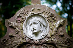 Woman face on tombstone. Old beautiful tombstone with carved woman face Royalty Free Stock Image
