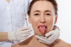 Woman face with tongue out isolated on white background. Cosmetic Treatment. Plastic Surgery. Face injections and collagen, funny. Face. Menopause. Doctor hands royalty free stock photo
