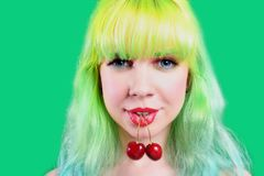 Woman face with two sweet cherry hanging from mouth on green background Stock Photo