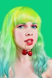 Woman face with two sweet cherry hanging from mouth on green background Royalty Free Stock Photography