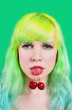 Woman face with two sweet cherry hanging from mouth on green background Stock Photos