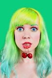 Woman face with two sweet cherry hanging from mouth on green background Stock Photography