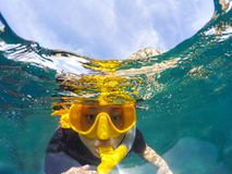 Woman face wearing snorkeling mask diving under clear sea water stock photo