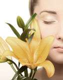 Woman face with yellow lily flower Royalty Free Stock Photography