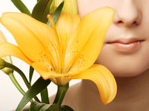 Woman face with yellow lily flower Royalty Free Stock Photos