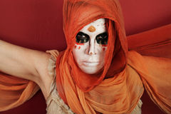 Woman in Facepaint. Woman in an orange scarf and wraith makeup Royalty Free Stock Photo
