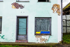 Woman faces on a house wall Stock Photo