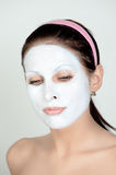 Woman with facial cream. A studio portrait of a young woman with her face covered with white facial cream Stock Photos