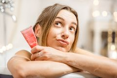 Woman with facial cream in the bathroom. Close-up portrait of a pretty woman holding facial cream tube lying in the retro bathroom Royalty Free Stock Photo