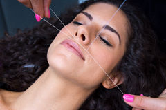 Woman on facial hair removal threading procedure royalty free stock photography