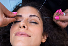 Woman on facial hair removal threading procedure. Attractive woman in beauty salon on facial hair removal eyebrow threading procedure Stock Images