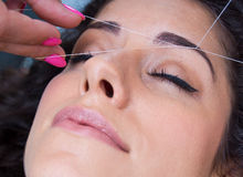 Woman on facial hair removal threading procedure. Attractive woman in beauty salon on facial hair removal eyebrow threading procedure Stock Photo