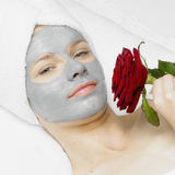 Woman with facial mask. Portrait of woman with facial mask holding a rose Stock Images
