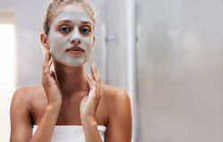 Woman with facial mask in bathroom. Close up shot of woman with facial mask in bathroom. Beautiful female doing beauty treatment after bath Stock Images