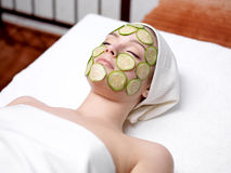 Woman with facial mask of cucumber. Young woman with facial mask of cucumber in beauty salon - indoors Stock Images
