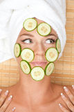 Woman with facial mask of cucumber Stock Image