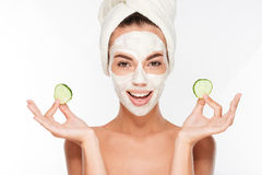 Woman with facial mask and cucumber slices in her hands. On white background Stock Image