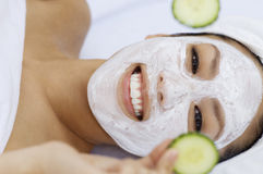 Woman with facial mask holding cucumber slices. Closeup portrait of a young woman with facial mask holding cucumber slices stock photo