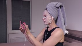 Woman with facial mask using smart phone. In room stock video footage