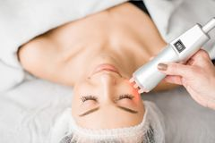 Woman during a facial massage. Young woman during a facial massage with professional tool at the medical center royalty free stock photos
