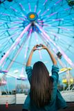 Woman Facing Ferris Wheel While Making Heart Hand Sign stock images